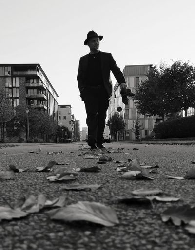 Man standing on street against buildings in city