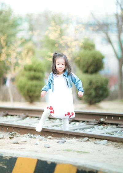 Portrait Of A Girl Playing On Railway Tracks