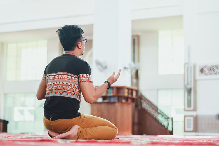 Rear view of man praying at mosque