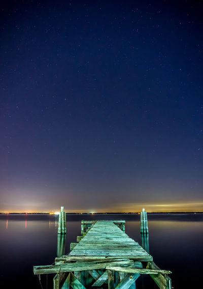 Pier over sea against blue sky at dusk