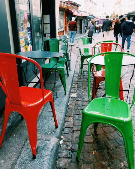 Colorful chairs and tables Cafe City City City Life Day Empty Furniture Furniture Design Green Green Color Lifestyles Local Local Cafe Outdoors People Red se Paris Street Street Photography Streetphotography Unrecognizable People Cornershop Neigborhood The Shop Around The Corner