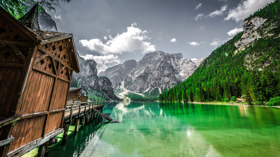 Scenic view of lake pragser wildsee by mountains against sky