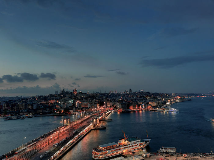 Aerial view of illuminated city by sea against sky at dusk
