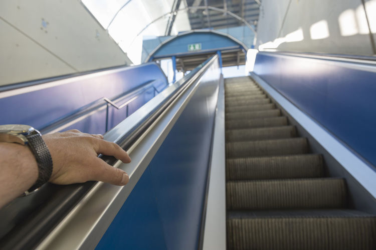 Cropped Hand Of Man Moving Up On Escalator