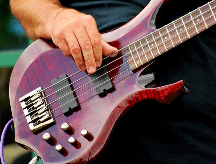 Close-up of man playing bass guitar