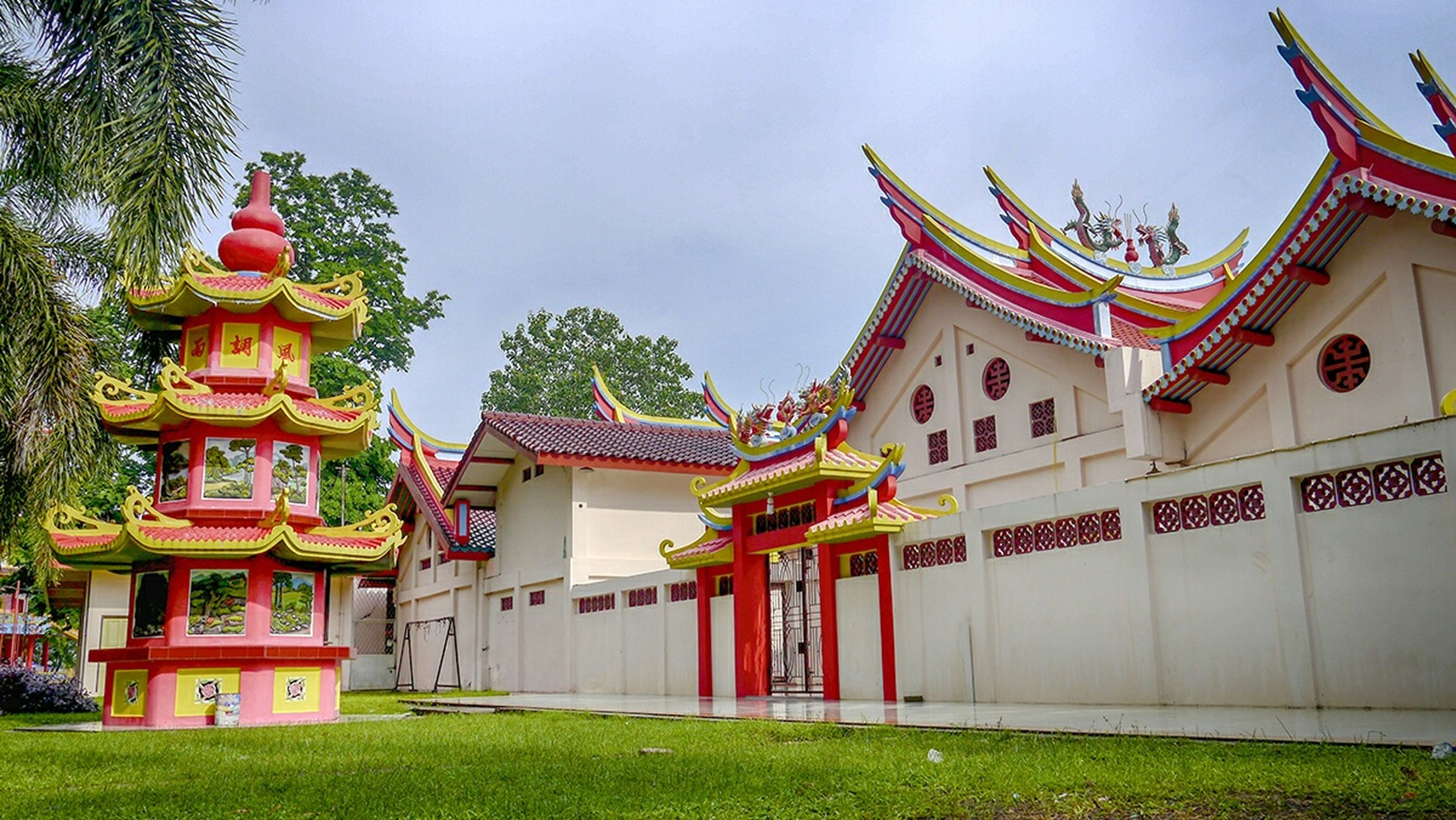 architecture, building exterior, built structure, religion, place of worship, temple - building, spirituality, sky, tree, tradition, low angle view, cultures, multi colored, outdoors, day, temple, roof, history, red
