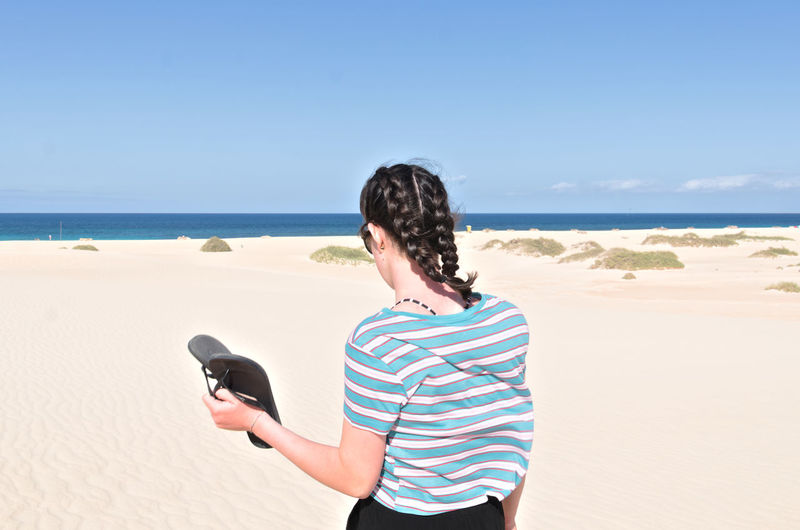 Rear view of teenage girl with braided hair standing on beach against sky