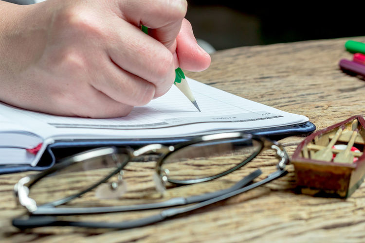 Close-up of hand writing in book by eyeglasses and model boat