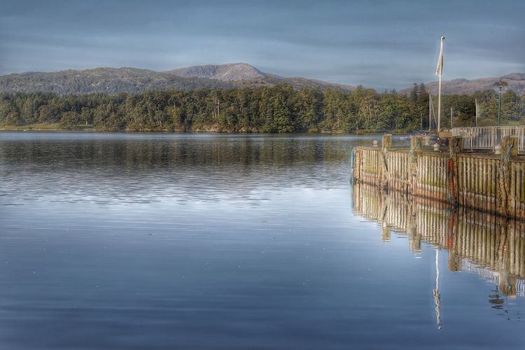 Wooden Pier Reflecting In Calm Lake With Wooded Lakeshore In Distance