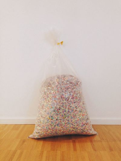 Confetto In Plastic Bag Against White Wall
