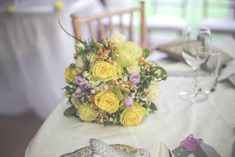 Close-Up Of Rose Bouquet On Table During Wedding