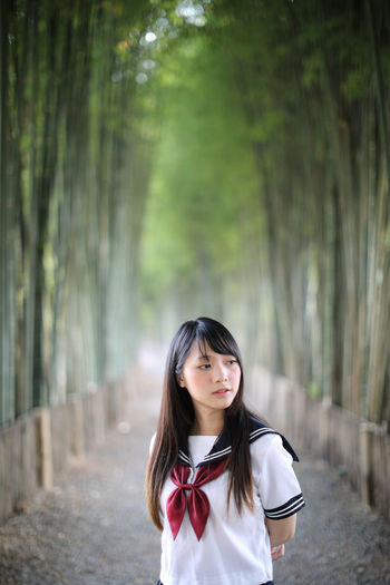 Young woman looking away while standing amidst bamboo groove
