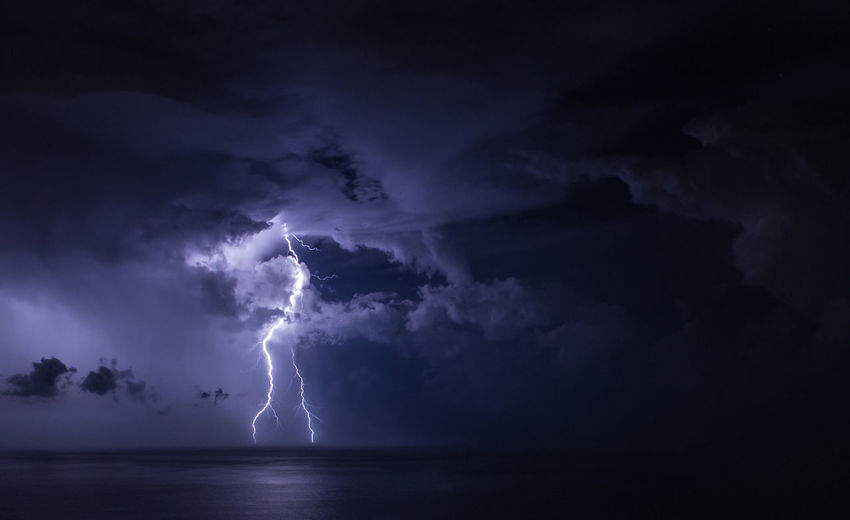 Lightning over sea against storm clouds in sky at night