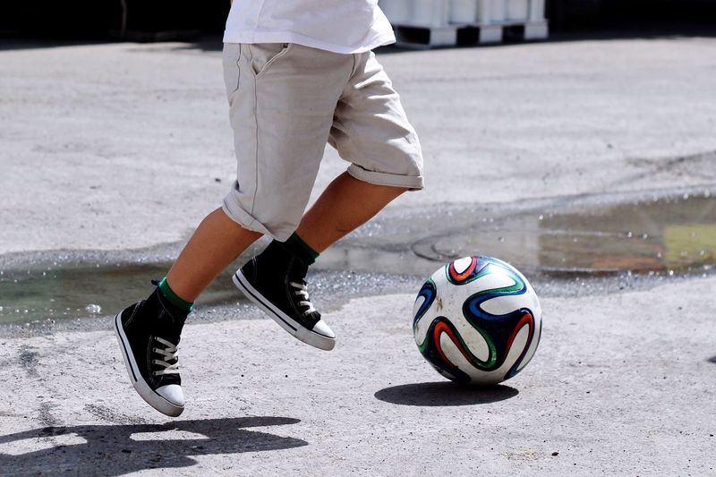 Low Section Of Person Playing Soccer On Sunny Day
