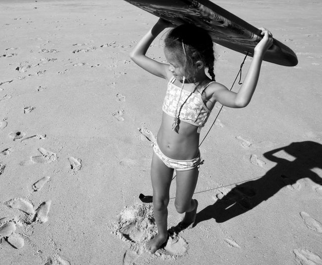 High angle view of girl carrying surfboard on head at beach