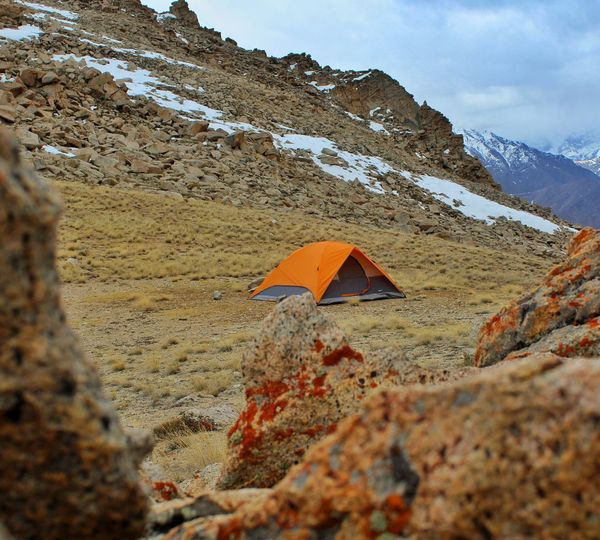 High angle view of tent on rocky mountain against sky