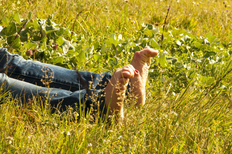 Low section of woman relaxing on grassy field