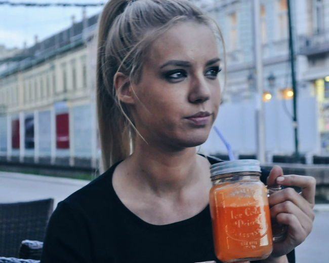 Close-up of young woman with drink in city
