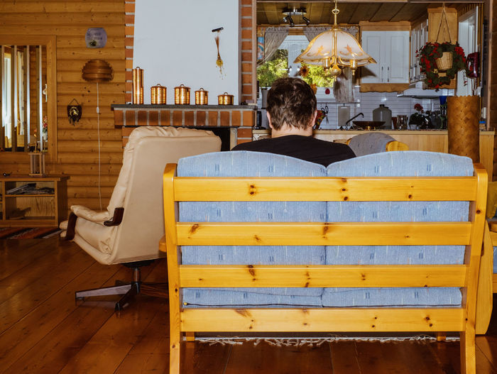 Rear view of man sitting on chair at home