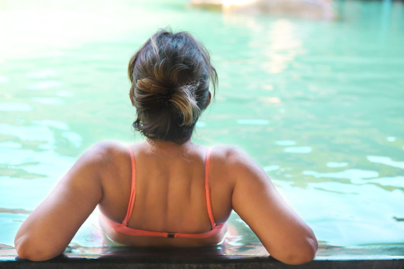 Rear view of woman relaxing in swimming pool