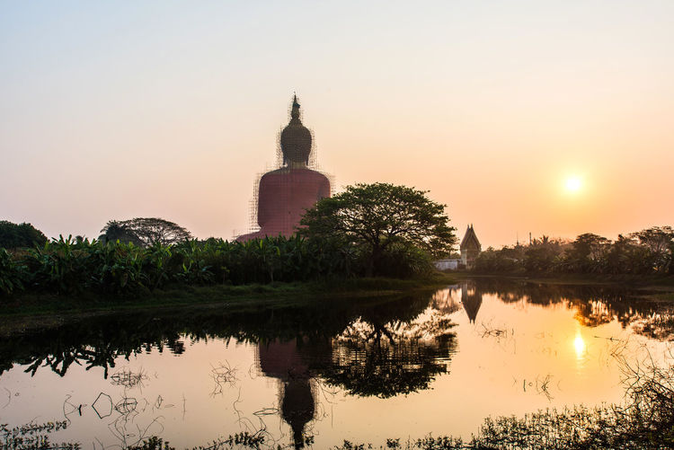 big Buddha in morning time with reflection on water Morning Warm Buddhist Politics And Government Tree Water Dawn Sunset Lake Gold Business Finance And Industry Business Statue Reflecting Pool Reflection Lake Stupa
