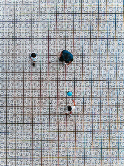Directly above shot of father and kids playing on tiled floor