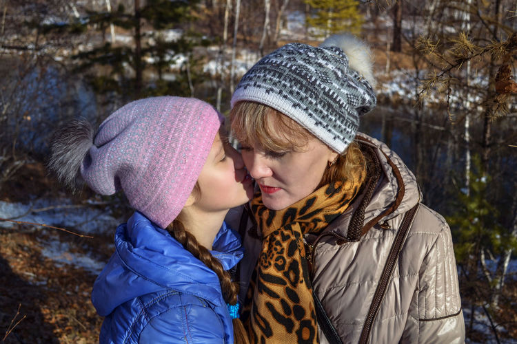 Daughter whispering in ear of mother during winter