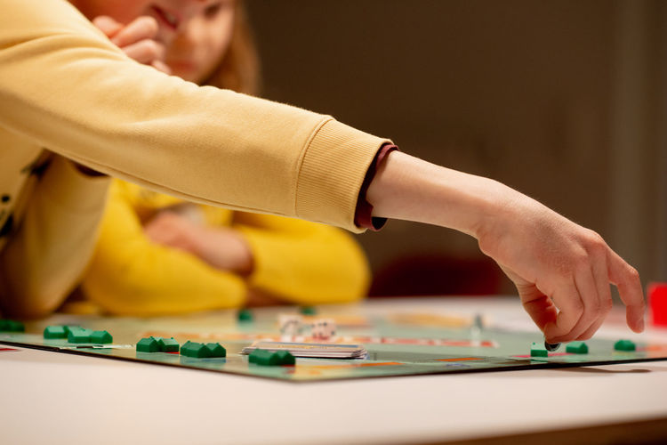 Midsection of people playing board game at home