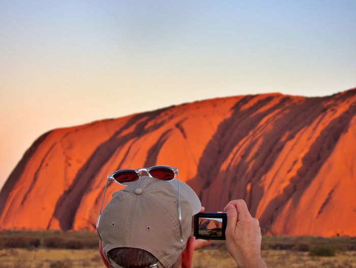 Rear view of man photographing with camera against mountains and sky