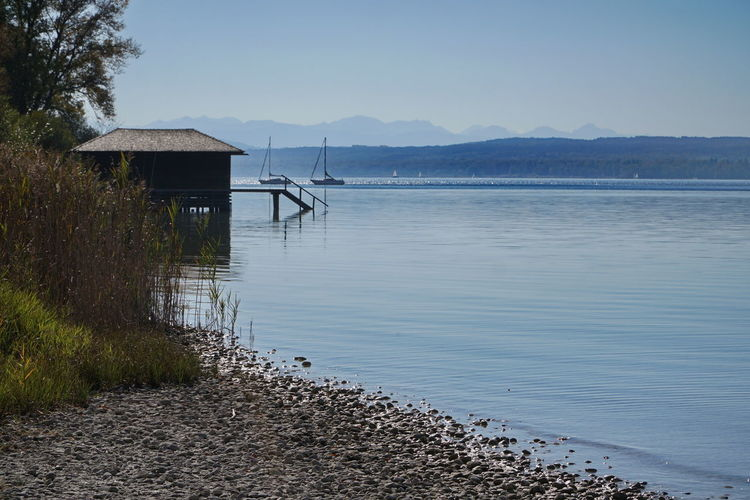 Boathouse and Alps Water Tranquility Architecture Scenics - Nature Tranquil Scene Built Structure Beauty In Nature No People Nature Sky Day Land Mountain Lake Plant Beach Environment Outdoors Non-urban Scene Ammersee Lake Ammersee Breitbrunn Sailing Vacations Time Off