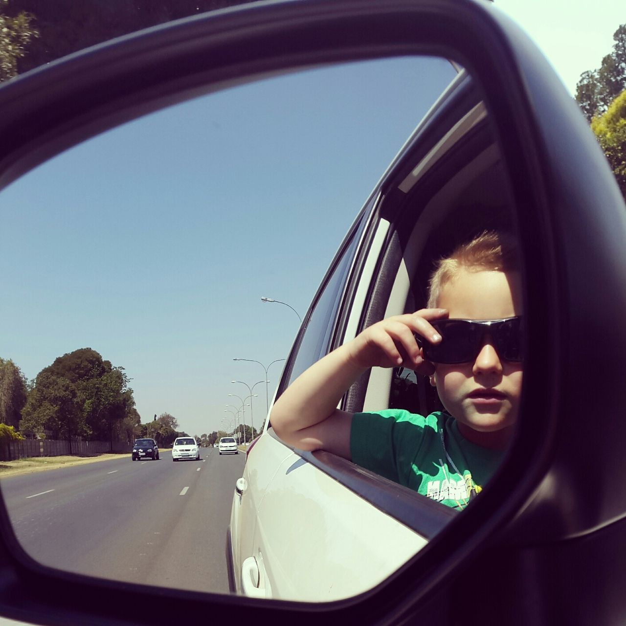 Reflection of boy wearing sunglasses in rear-view mirror of car