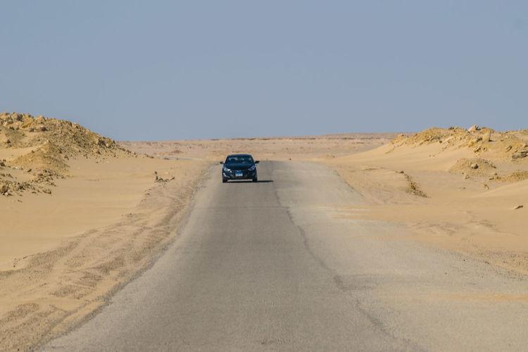Car On Road In Desert Against Clear Sky