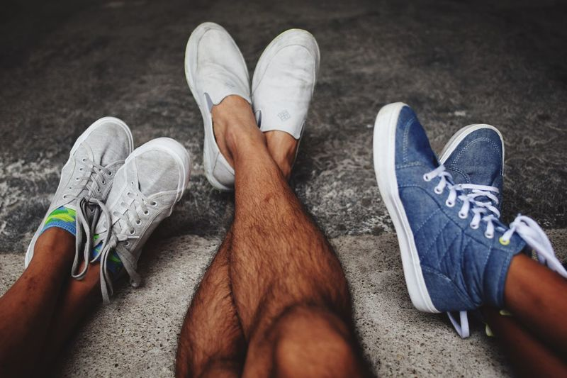 Low section of male friends wearing shoes
