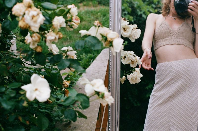 Midsection of woman standing by white flowers
