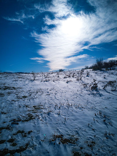 Scenic view of snowcapped landscape against blue sky