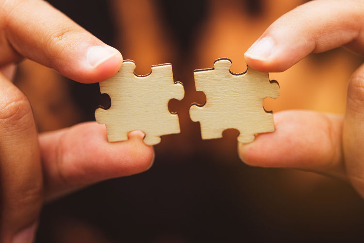 Cropped hands holding jigsaw puzzles