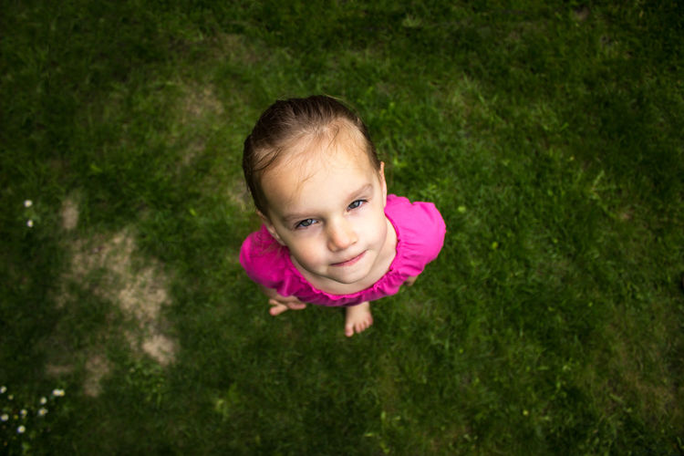 High Angle Portrait Of Cute Girl Standing On Grassy Field