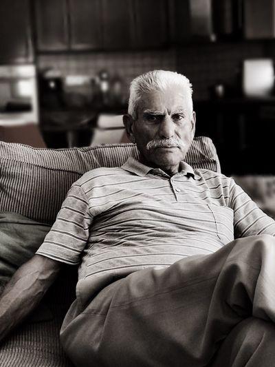 Portrait of senior man sitting on sofa at home