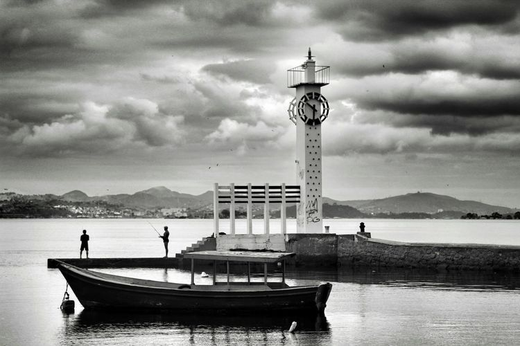 Boat Moored In Lake Against Lighthouse And Cloudy Sky At Dusk