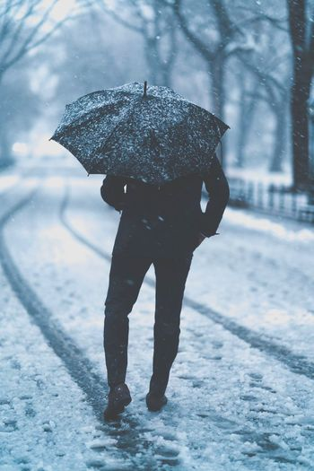 Rear view of man with umbrella walking on wet road during snowfall