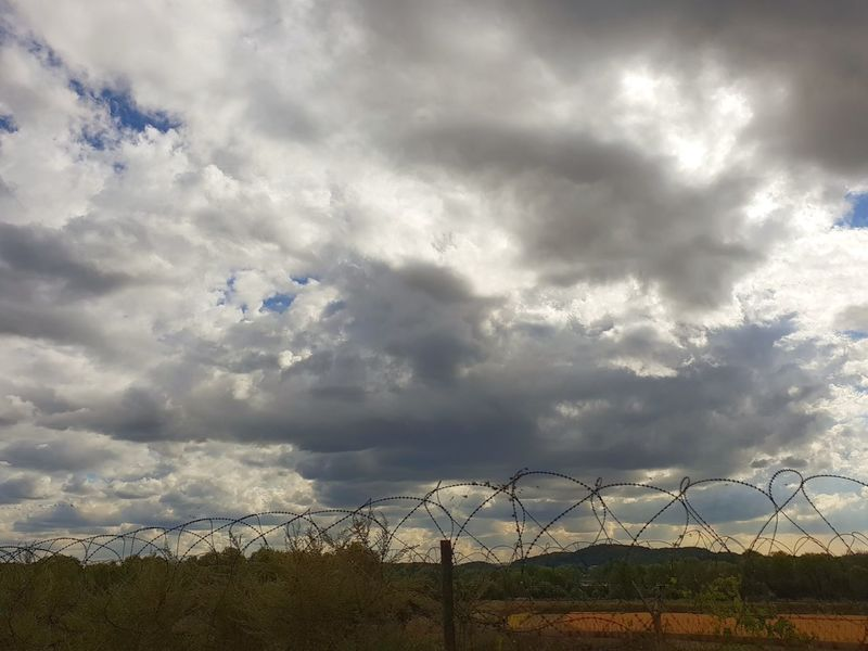 EyeEmNewHere EyeEm Best Shots Nature Rear View Countryside Moody Sky Beautiful View Oil Pump Protection Security Sky Cloud - Sky Chainlink Fence Storm Cloud Dramatic Sky Fence Sky Only Storm Atmospheric Mood Wire Mesh