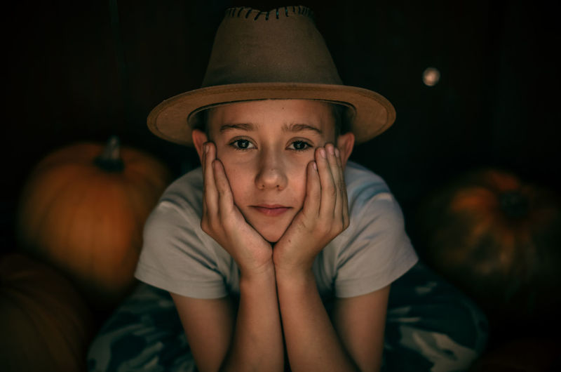 Portrait of cute boy with hands on cheek by pumpkin
