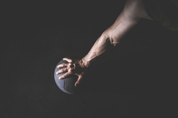Close-up of hand holding basketball over black background