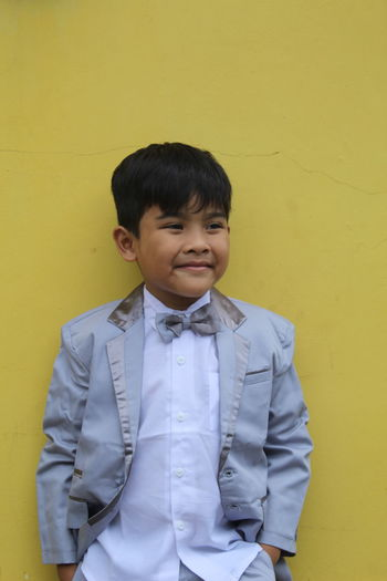 Portrait of boy standing against yellow wall