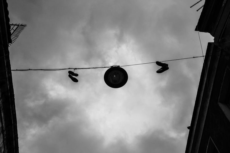 Low angle view of silhouette lanterns hanging against sky
