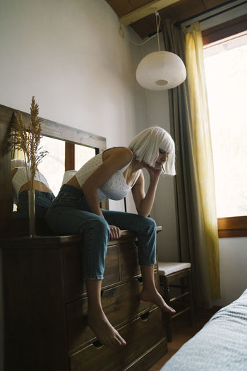 Side view of woman sitting on seat at home