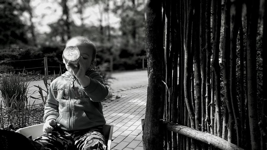 Boy Having Drink While Sitting By Fence