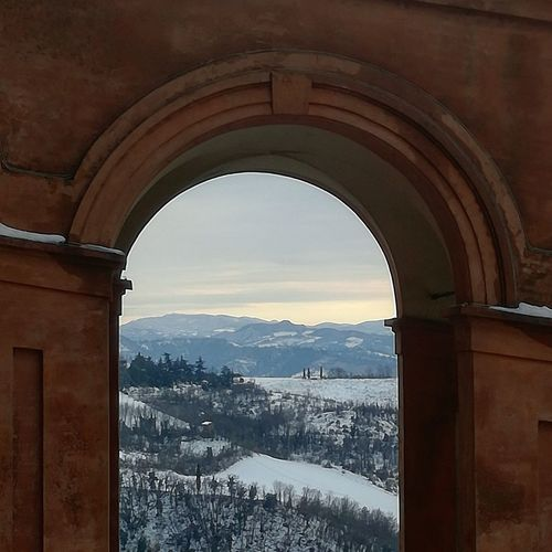 View of mountain seen through window during winter