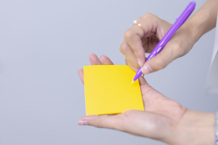 Midsection of woman holding paper against white background
