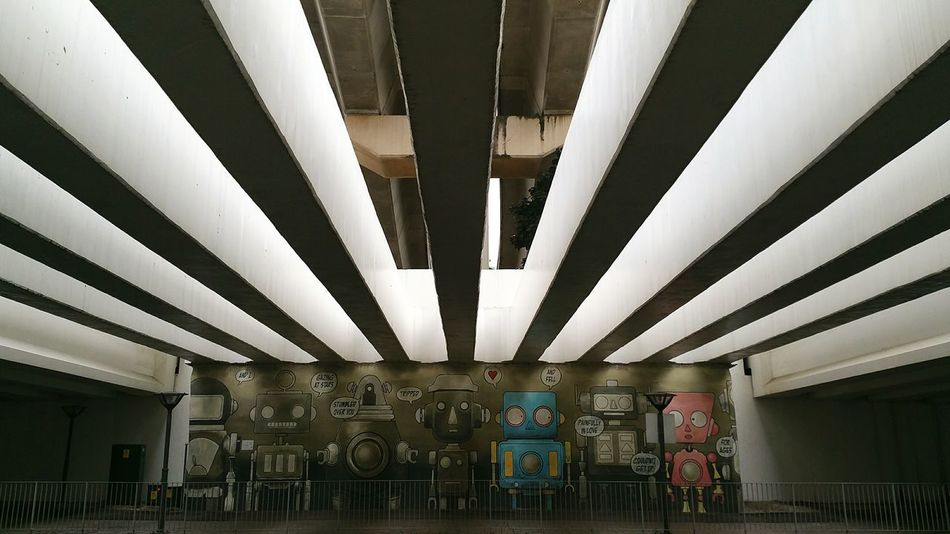 Wall mural at a pedestrain underpass No People Day Neighbourhood Wall Art Wall Murals Graffiti Art Underpassview Underpass Contrast Strips Of Light Park Parkconnector ArtWork VisualArt  Robots Robot Love Poems Art Stripes Pattern